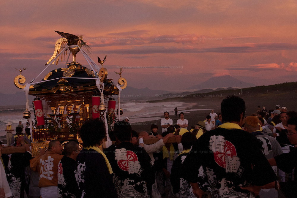 Mikoshi are carried into the sea with mount Fuji in the background during the Hamaorisai Matsuri that takes place on Southern Beach in Chigasaki, near Tokyo, Kanagawa, Japan Monday July 18th 2011. The festivals marks the celebration of Marine Day and the rescuing of a divine image that was washed ashore in the area. Over thirty Mikoshi or portable shrines are carried through the night from surrounding shrines to arrive on the beach for sunrise. There they are blessed and then carried into the surf to purify them.