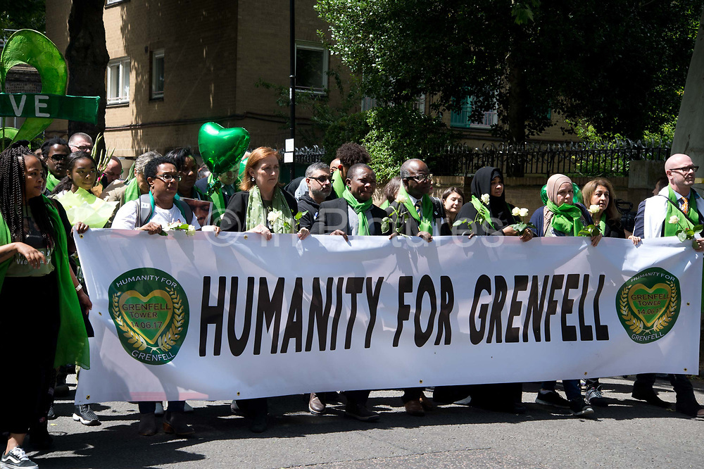 Commemoration of the first anniversary of the devastating fire of 14th/15th June  2017 in Grenfell Tower, Lancaster West Estate, West London, United Kingdom when 72 people were killed. After a 72 second silence one second for each victim survivors and family members held a silent walk to the tower, many walking behind a banner saying Humanity for Grenfell.