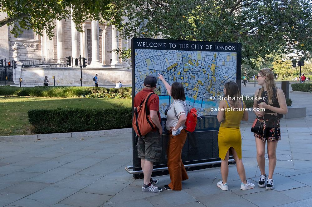 With the pillars and architecture of St Paul's Cathedral in the distance, visitors to London stop to view a detailed map of the City of London, the capital's historic financial district, on 8th September 2021, in London, England.