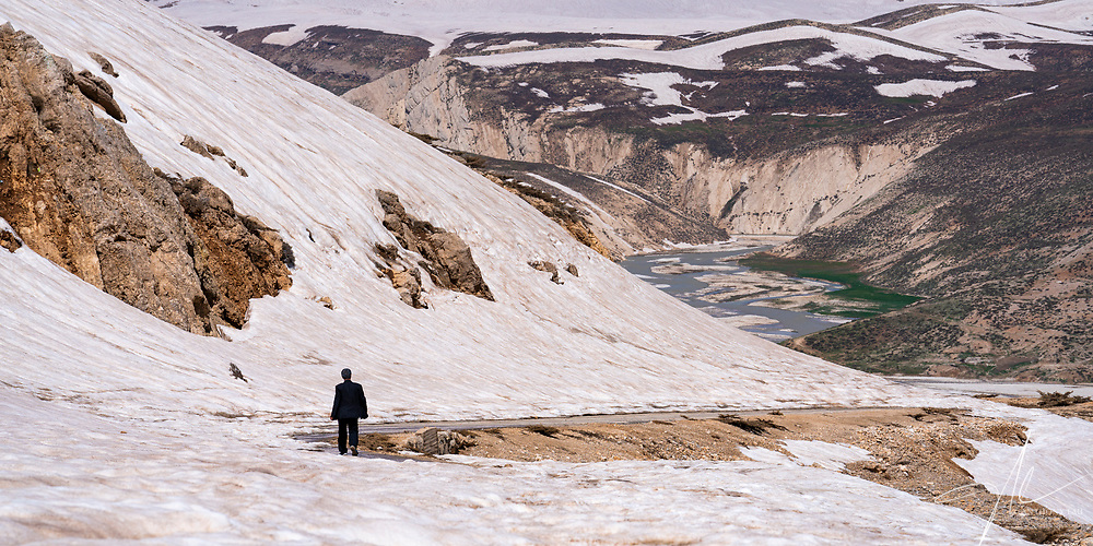 A local walking back to his home pass the glacier in Zagros Mountain.