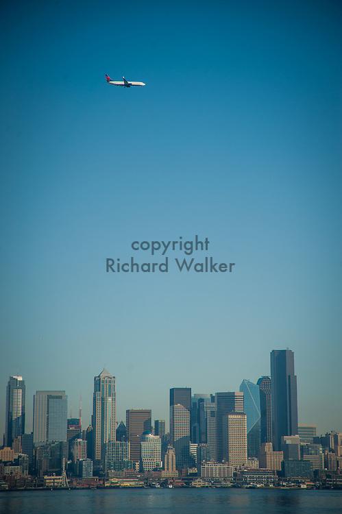 2017 NOVEMBER 06 -  A Delta airplane flies over Downtown Seattle skyline seen from Alki, Seattle, WA, USA. By Richard Walker