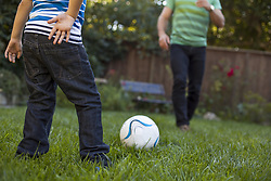 Oct. 23, 2014 - Father and son playing football in garden (Credit Image: © Image Source/Image Source/ZUMAPRESS.com)