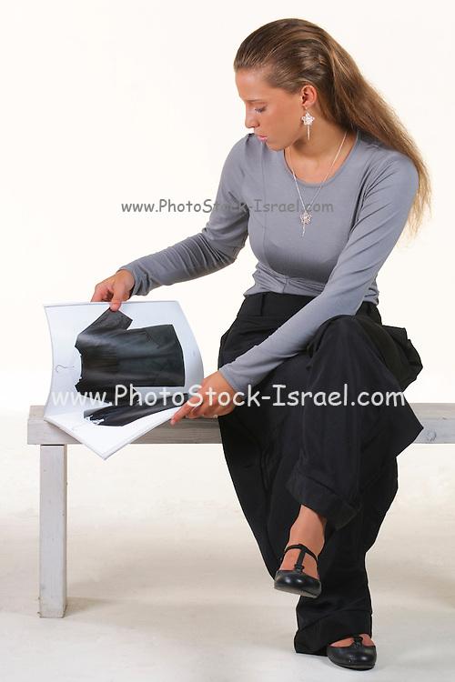 young Fashionable woman reads a fashion magazine