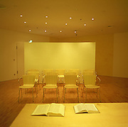 Empty chairs and open Bibles, all bathed in yellow artificial light make this airport chapel in Frankfurt am Main, Germany a European modernist haven from the chaos of global air travel; an escape from delays, terrorism and overall fears of flying. Predominately Christian with small corners for Muslim believers, the new modernism at Frankfurt/Main reflects a strong European tradition of functional design ? far removed from the drab, dourness of many similar American facilities. Picture from the 'Plane Pictures' project, a celebration of aviation aesthetics and flying culture, 100 years after the Wright brothers first 12 seconds/120 feet powered flight at Kitty Hawk,1903. .