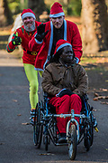 Wheelchair Santas were self-propelled or were assisted by helpers, some on roller blades - 2000 Santas of all ages take part in the annual Santa Run in Battersea Park to support Noah's Ark Children's Hospice.