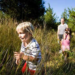 A woman and her young children hike through a grassy field near the Eightmile River in Lyme, Connecticut.  The Nature Conservancy's Pleasant Valley Preserve.