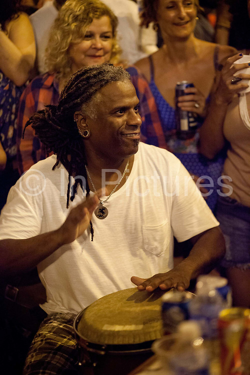 Drummer man playing a drum and smiling, Pedra do Sal, the birthplace of Samba, in Gamboa district which was the neighbourhood where the ex slaves lived after abolition, sometimes referred to as the first favela. Rio de Janeiro, Brazil