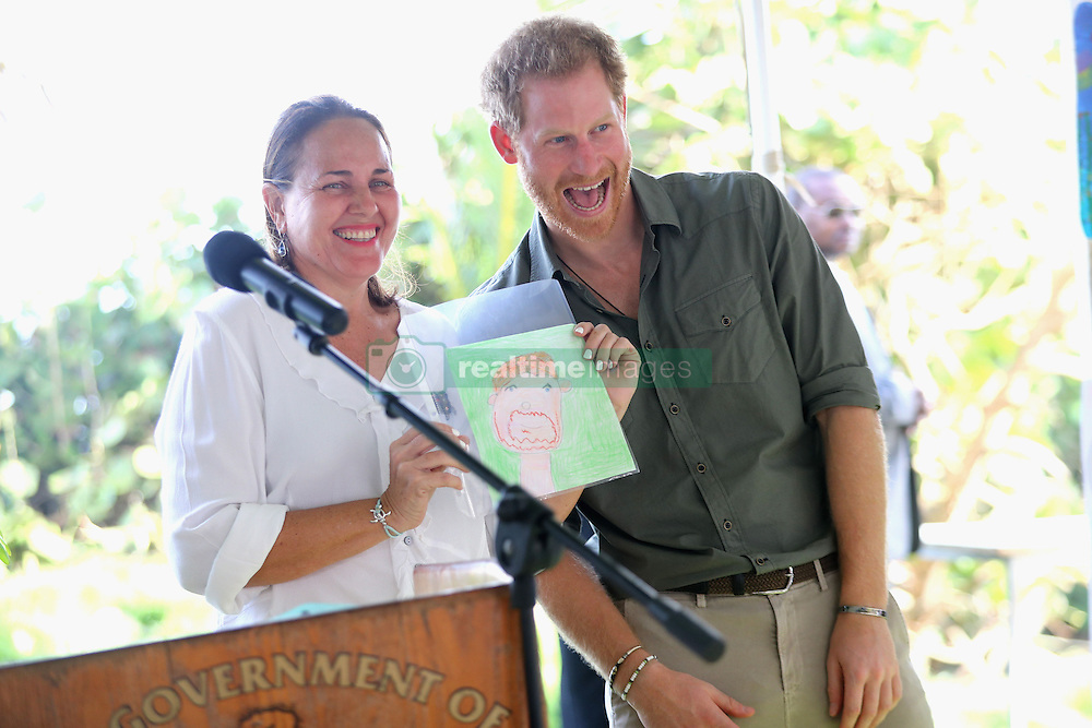 Prince Harry looks at a portrait of himself which was drawn by a child, during a visit to a Turtle Conservation Project at Colonarie Beach, Saint Vincent and the Grenadines, during the second leg of his Caribbean tour.