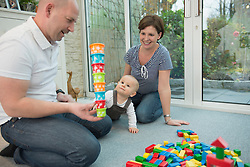 Parents and little son sitting on ground of living room playing together