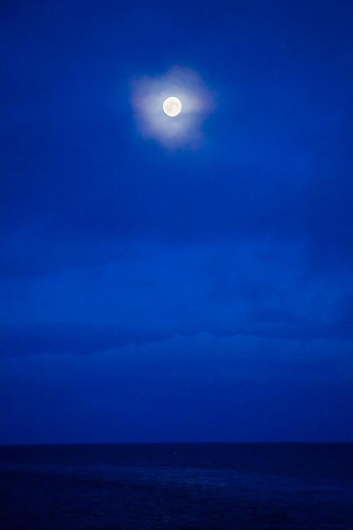 A full moon shines over the Norwegian Sea, Lofoten Islands, Norway.