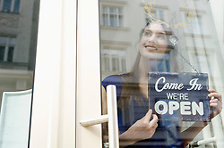Sales girl holding opening board of fashion shop, smiling