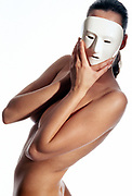 Nude woman holding white ceramic mask on face