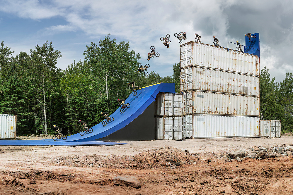 Drew Bezanson had a dream. He wanted to build a huge BMX park at the back of his friends property in his hometown of Truro, Nova Scotia using only wood and shipping containers. They first started by clearing trees and levelling the dirt. It took months to prepare and build all the features because it rained so hard everyday that the mud created made it impossible to move material around. Finally, we got our shooting window which was only a couple hours each day during a week in August, but only after the morning showers let up and just before the evening rain started again. We plugged away slowly that week creating more and more shots, saving this flat drop, the biggest of the entire set up, till the very last day. He had a few tricks in mind he was going to do but hadn't made up his mind about doing a backflip yet. The consequences were high and nothing of this size with a flat take off had ever been flipped before. Something in his head triggered and he yelled lets do it before being lifted on top by a crane. I was ready, shaking a bit, knowing I was only getting one chance for the shot, land or slam. My favourite part of the shot is the expression on his face in the landing frames.