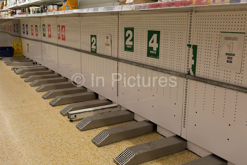 As the UK government announces further Coronavirus-related restrictions to its citizens, with the immediate closure of pubs, cafes, gyms and cinemas, and the worldwide number of deaths reaching 10,000 with 240,000 cases, 953 of those in London alone, there are empty spaces where milk was sold at a Sainsburys supermarket in East Dulwich, on 20th March 2020, in London, England.