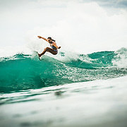 Female surfer shredding on her short board in Pavones, Costa Rica.