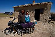 Mongolian Shepherds Ge Ri Li Ao De, left and his wife Ao Te Gen, with their motorbike and house, with solar panels, Inner Mongolia, China