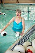 Senior living women looking at camera doing water aerobics