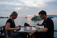 Two travelers from England play cards at sunset on the waterfront in Kota Kinabalu, Sabah, Malaysia. (August 9, 2019)