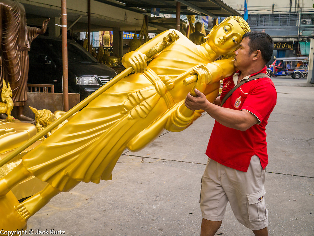 """12 NOVEMBER 2012 - BANGKOK, THAILAND:   A man delivers an unfinished Buddha statue to a workshop on Bamrung Muang Street in Bangkok. Thanon Bamrung Muang (Thanon is Thai for Road or Street) is Bangkok's """"Street of Many Buddhas."""" Like many ancient cities, Bangkok was once a city of artisan's neighborhoods and Bamrung Muang Road, near Bangkok's present day city hall, was once the street where all the country's Buddha statues were made. Now they made in factories on the edge of Bangkok, but Bamrung Muang Road is still where the statues are sold. Once an elephant trail, it was one of the first streets paved in Bangkok. It is the largest center of Buddhist supplies in Thailand. Not just statues but also monk's robes, candles, alms bowls, and pre-configured alms baskets are for sale along both sides of the street.    PHOTO BY JACK KURTZ"""