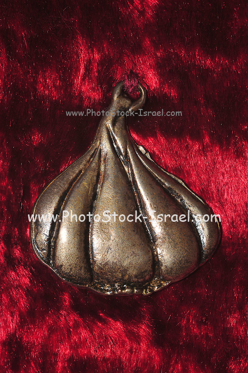 decorated silver good luck charm on red velvet background