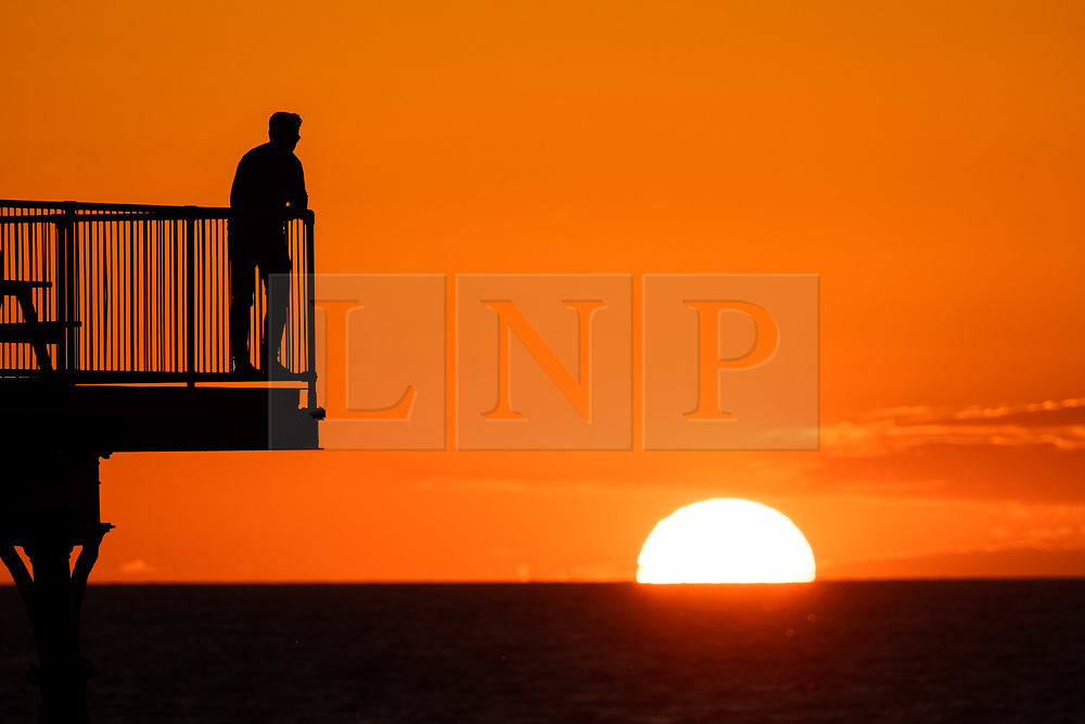 ©Licensed to London News Pictures<br /> 11/05/2019. Aberystwyth, UK. People are silhouetted against the glorious setting sun as they stand and pose for photographs on the pier in Aberystwyth on the Cardigan Bay coast, West Wales. The weather is set to get warmer again in the coming week after as period of unsettled cold conditions. Photo credit Keith Morris/LNP