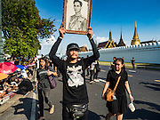 15 OCTOBER 2016 - BANGKOK, THAILAND: A man holds up a portrait of Bhumibol Adulyadej, the King of Thailand, while he walks past the Grand Palace in Bangkok. King Bhumibol Adulyadej died Oct. 13, 2016. He was 88. His death comes after a period of failing health. With the king's death, the world's longest-reigning monarch is Queen Elizabeth II, who ascended to the British throne in 1952. Bhumibol Adulyadej, was born in Cambridge, MA, on 5 December 1927. He was the ninth monarch of Thailand from the Chakri Dynasty and is known as Rama IX. He became King on June 9, 1946 and served as King of Thailand for 70 years, 126 days. He was, at the time of his death, the world's longest-serving head of state and the longest-reigning monarch in Thai history.      PHOTO BY JACK KURTZ