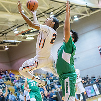 Gallup Bengal Quincy Smith (20) attempts a reverse layup over Farmington Scorpion Kobe Shorty (55) at Gallup High School Tuesday.