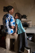 """Ayuba Ahmed, 38, and her daughter Asia Temame, 5, in their kitchen next to their new fuel saving stove. Ayuba belongs to the """"Hawig Gudina"""" (We Aspire for Hope) fuel saving stove producer group in Dodota Alem Village, Ethiopia, produces stoves that save women time on firewood collection and food preparation. On average women have reduced their cooking time by more than half by switching from their traditional stoves to the fuel efficient model. Sara A. Fajardo/Catholic Relief Services"""