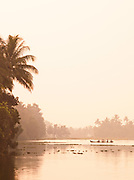 A canoe transport glides along the water in the Keralan Backwaters in India