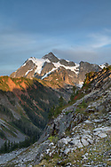 Sunset light on Mount Shuksan from the Artist Point to Huntoon Point trail along Kulshan Ridge in Washington State's North Cascades Range. Photographed from Kulshan Ridge in the Mount Baker Wilderness. Mount Shuksan itself lies in North Cascades National Park.