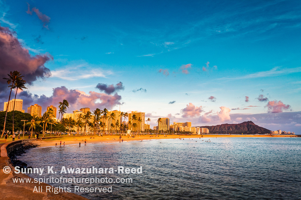 Magic Island Beach at sunset. Sunset glow on Waikiki skyline and Diamond Head. Honolulu, Oahu Island, Hawaii.