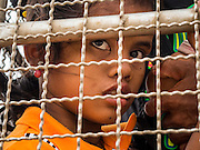 16 JUNE 2014 - ARANYAPRATHET, THAILAND: A Cambodian child locked in a Thai immigration police truck in Aranyaprathet, Thailand. More than 150,000 Cambodian migrant workers and their families have left Thailand since June 12. The exodus started when rumors circulated in the Cambodian migrant community that the Thai junta was going to crack down on undocumented workers. About 40,000 Cambodians were expected to return to Cambodia today. The mass exodus has stressed resources on both sides of the Thai/Cambodian border. The Cambodian town of Poipet has been over run with returning migrants. On the Thai side, in Aranyaprathet, the bus and train station has been flooded with Cambodians taking all of their possessions back to Cambodia. PHOTO BY JACK KURTZ