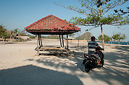 Indonesia, Lombok. Riding motorbike on Kuta Beach in a late afternoon in August.