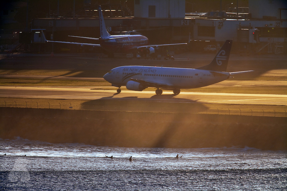 Surfers wait for the next wave at Lyall Bay while an Air New Zealand aircraft gathers speed at the Wellington International Airport.
