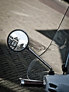 Reflection of typical canal houses in the sideview mirror of a scooter.