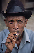 Batak man wearing hat and smoking cigarette..Batak Indigenous Christian people living on Samosir Island and nearby Lake Toba in Indonesia. There are some 6 million Christian Batak in Indonesia, the world's largest Muslim country of 237 million people, which has more Muslims than any other in the world. Though it has a long history of religious tolerance, a small extremist fringe of Muslims have been more vocal and violent towards Christians in recent years. ..Batak religion is found among the Batak societies around Lake Toba in north Sumatra. It is ethnically diverse, syncretic, liable to change, and linked with village organisations and the monotheistic Indonesian culture. Toba Batak houses are boat-shaped with intricately carved gables and upsweeping roof ridges, and Karo Batak houses rise up in tiers. Both are built on piles and are derived from an ancient Dong-Son model. The gable ends of traditional houses, Rumah Bolon or Jabu, are richly decorated with the cosmic serpent Naga Padoha carved in wood or in mosaic, lizards, double spirals, female breasts, and the head of the singa, a monster with protruding eyes that is part human, part water buffalo, and part crocodile or lizard. The layout of the village symbolises the Batak cosmos. They cultivate irrigated rice and vegetables. Irrigated rice cultivation can support a large population, and the Toba and the Karo live in densely clustered villages, which are limited to around ten homes to save farming land. The kinship system is based on marriage alliances linking lineages of patrilineal clans called marga. In the 1820's Islam came to the southern Angkola and Mandailing homelands, and in the 1850's and 1860's Christianity arrived in the Angkola and Toba region with Dutch missionaries and the German Rheinische Mission Gesellschaft. The first German missionary caused the Dutch to stop Batak communal sacrificial rituals and music, which was a major blow to the traditional religion. Dutch colonial policy favoured Chri