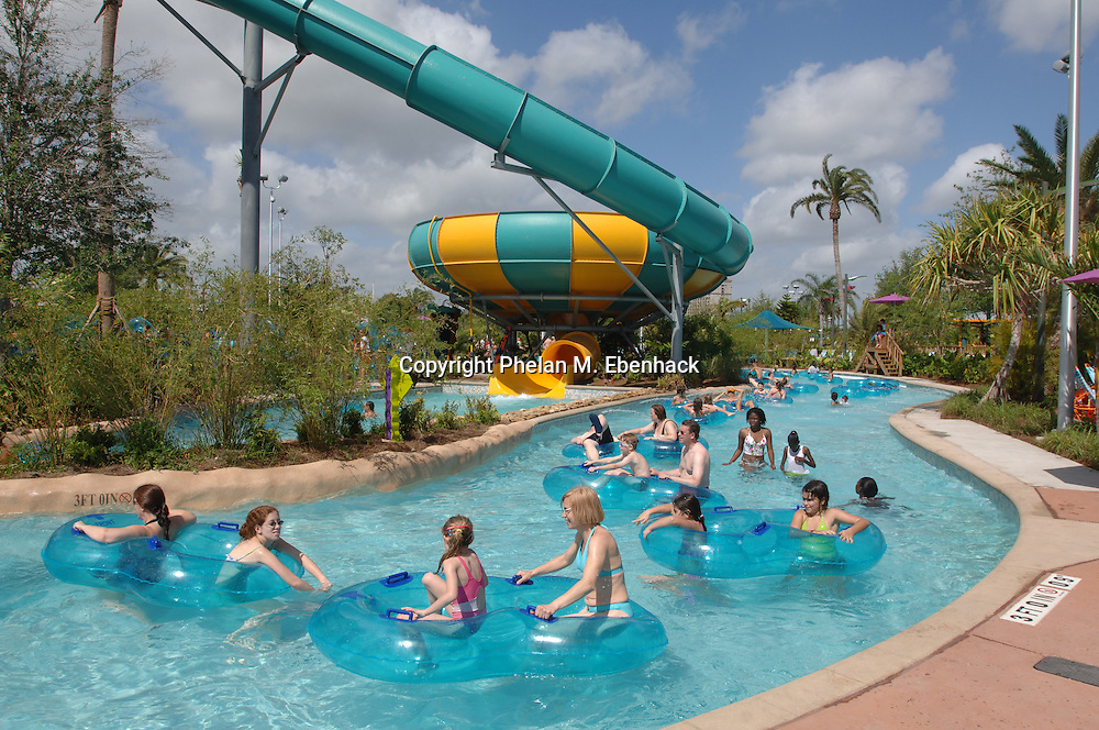 Park guests float on the Loggerhead Lane lazy river past the Tassie's Twisters ride at Sea World's new waterpark Aquatica in Orlando, Florida.