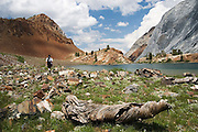 A male hiker walks in a meadow bounded by colorful rock cliffs along a trail above Convict Lake, near Mammoth Lakes in the Eastern Sierras, California.