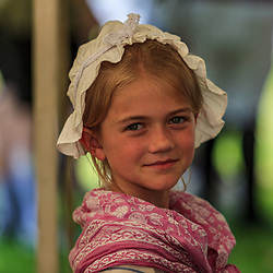 Lancaster, PA, USA - June 9. 2012: Small colonial child wearing a white house cap at a British America reenactment camp.