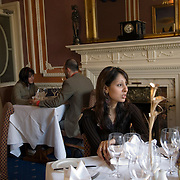 Young woman of pakistani originssitting alone at table in elegant restaurant<br />