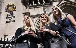 © Licensed to London News Pictures. 23/04/2021. London, UK. Former Post Office sub-postmaster Janet Skinner (C) is supported by niece Hayley Adams (L) and daughter Toni Sisson outside The High Court. The Appeal Court has cleared the names of a group of 42 sub-postmasters - some of whom were jailed for stealing money after the Horizon accounting software was installed at Post Offices. At a previous High Court hearing a judge found the Fujitsu accounting system had major faults and defects. The Post Office has already agreed to pay £58m in a settlement with more than 500 sub-postmasters. <br /> Six convictions were overturned last year . Photo credit: Peter Macdiarmid/LNP