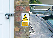 © Licensed to London News Pictures. 27/11/2014. Fetcham, UK. A CCTV sign on the property.  A manhunt is under way across two counties after a man and woman were found stabbed to death in Surrey. The bodies were found at a house in Fetcham, near Leatherhead, after Surrey Police were alerted in the early hours.. Photo credit : Stephen Simpson/LNP