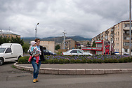 Stepanakert, Nagorno-Karabakh - September 25, 2016: A woman carries a child across a street in Stepanakert, capital of the disputed region of Nagorno Karabakh, locally known as the Republic of Artsakh.<br /> <br /> (September 25, 2016)