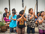 """23 JUNE 2015 - MAHACHAI, SAMUT SAKHON, THAILAND: People kneel in the street and pray during the City Pillar Shrine Procession in Mahachai. The Chaopho Lak Mueang Procession (City Pillar Shrine Procession) is a religious festival that takes place in June in front of city hall in Mahachai. The """"Chaopho Lak Mueang"""" is  placed on a fishing boat and taken across the Tha Chin River from Talat Maha Chai to Tha Chalom in the area of Wat Suwannaram and then paraded through the community before returning to the temple in Mahachai.   PHOTO BY JACK KURTZ"""