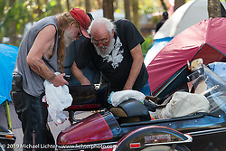 Tim Taylor helping his buddy Billy Mitchell do maintenance on his bike in their campground by the Cabbage Patch before the return ride of 4,600 miles to Washington state. Daytona Bike Week. FL, USA. March 12, 2014.  Photography ©2014 Michael Lichter.
