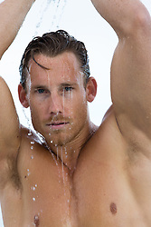 sexy man with water on his face and body