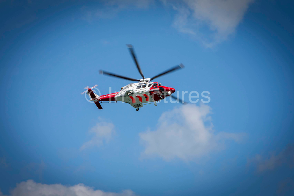 The HM Coastguard rescue helicopter G-C1JW  flying over the sea during a training exercise outside Folkestone Harbour, Folkestone, Kent. UK.
