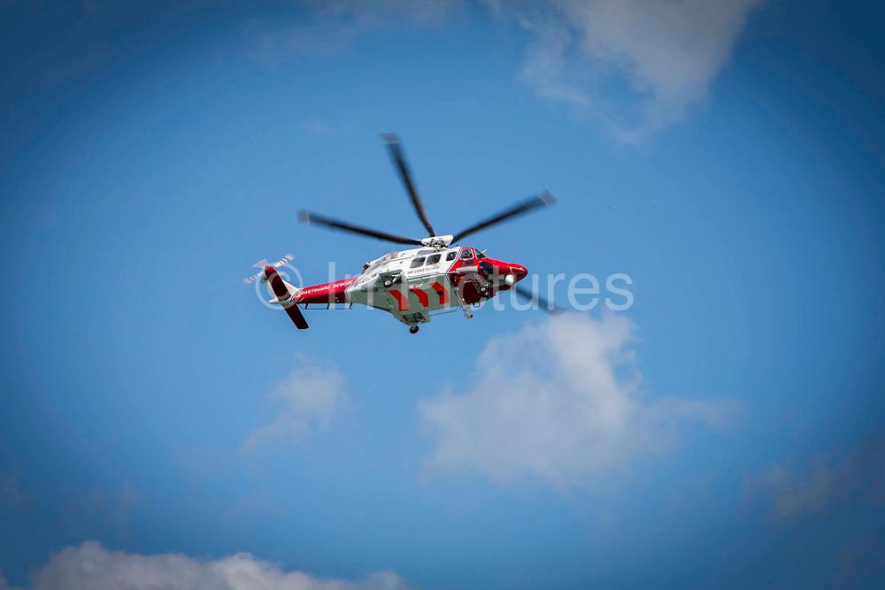 The HM Coastguard rescue helicopter G-C1JW  flying over the sea during a training exercise outside Folkestone Harbour, Folkestone, Kent. UK.