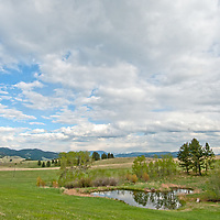 Cumulus clouds float over a pond and pastures in Montana's southern Bridger Mountains, near Livingston and Bozeman.