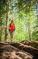 A woman walking a trail in the forest, Little Si trail, Washington, USA.